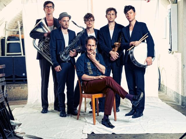 Die Band King Pepe und Le Rex posieren in einem Studio. Der Sänger sitzt auf einem Stuhl.