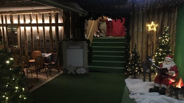 Eine Treppe, zkwei beleuchtete Plastsikchristbäume, ein Platiksamichlaus und warme Lichter. Der Eingang zum Samichlausbunker.