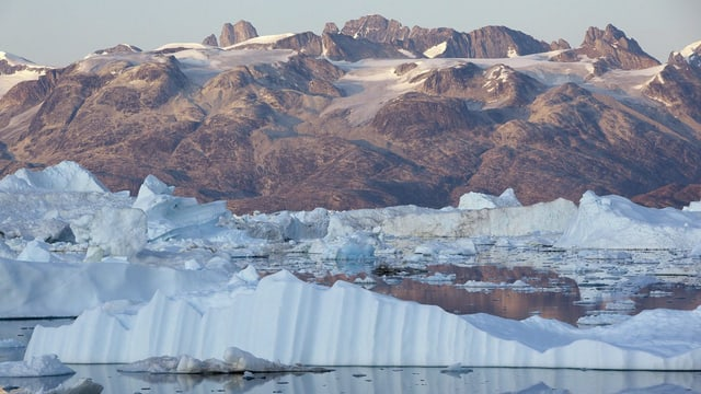 Eisberge vor kahlen Felsen an der grönländischen Küste.