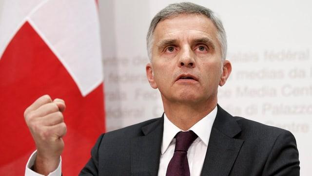 Aussenminister Didier Burkhalter ballt die Faust, dahinter ist die Schweizer Fahne.