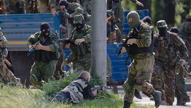 Prorussische maskierte Kämpfer halten ihre Waffen im Anschlag