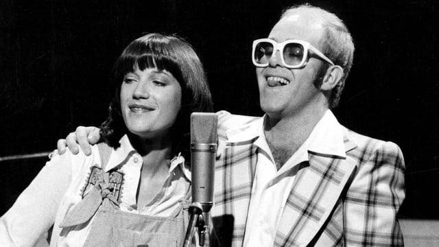 Schwarzweissfoto: Frau und Mann nebeneinander vor einem Mikrofon