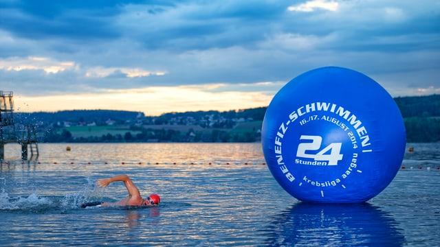 Jürg Ammann neben Wasserball mit Benefizschwimmen-Logo