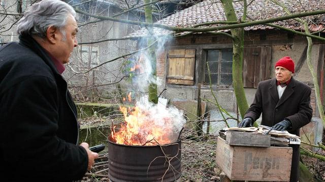 Zwei ältere Männer stehen neben einer brennenden Tonne in einem Vorstadt-Garten.