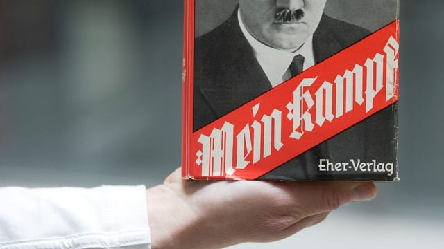Eine Hand hält ein Exemplar von «Mein Kampf».