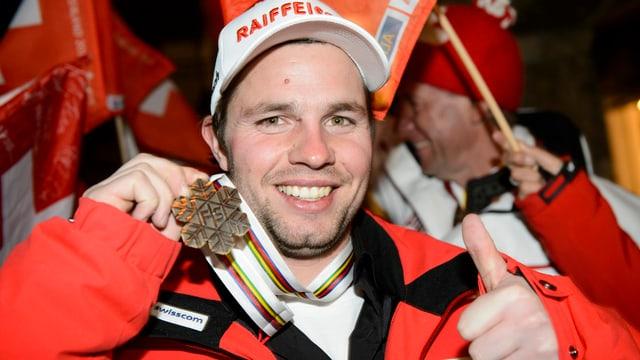Beat Feuz posiert mit seiner Bronzemedaille, dazu streckt er seinen linken Daumen nach oben.