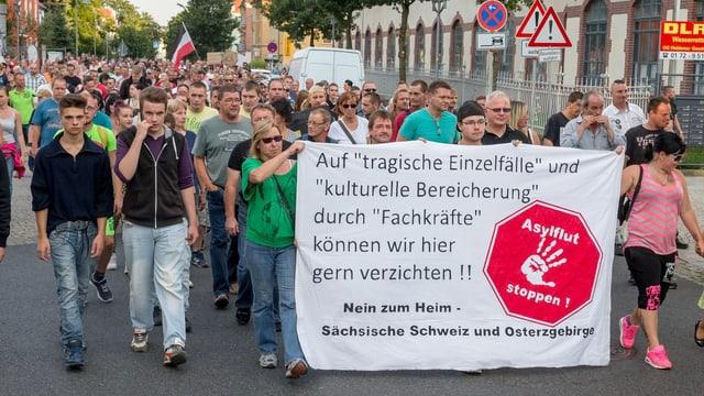 Demonstranten in Heidenau tragen ein asylkritisches Transparent vor sich her.