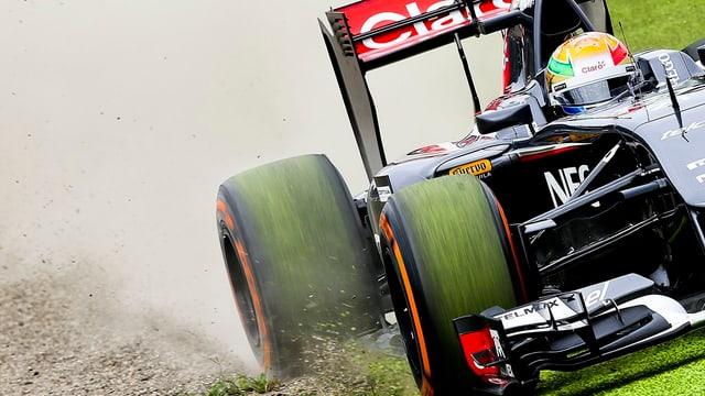 Ein Formel 1-Auto fährt durch Kies und Wiese.