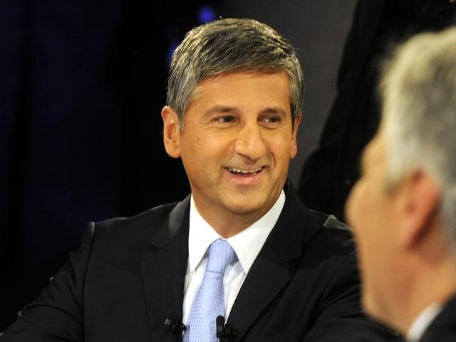 Michael Spindelegger lächelt und blickt dabei zur Seite. Auch er scheint sich in einem TV-Studio zu befinden. Er trägt einen dunklen Anzug und eine hellblaue Krawatte.