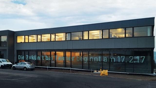 Neubau der Firma Tanner - Bürogebäude mit Glasfassade im Abendlicht