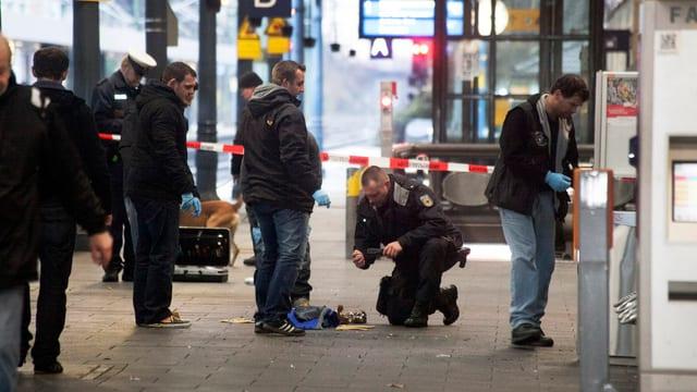 Polizisten untersuchen Reste einer Tasche am Bonner Hauptbahnhof.