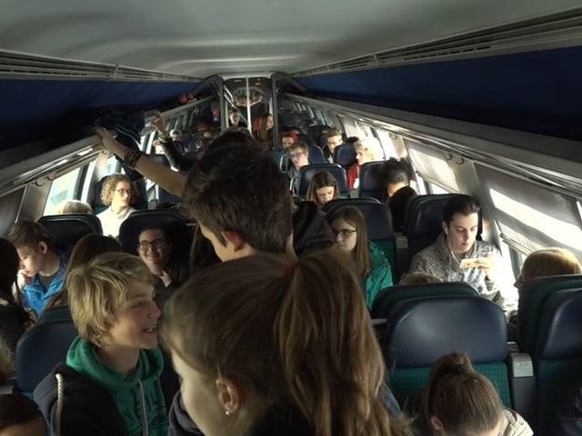 Jugendliche in einem überfüllten Zug.