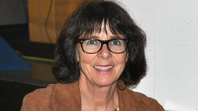 Portrait einer Frau mit dunklen, halblangen Haaren und mit Brille.