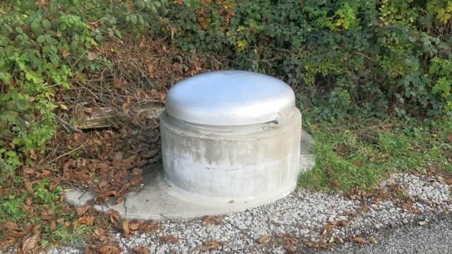 Gefasste Quelle. Rundes Betonelement mit Stahldeckel.