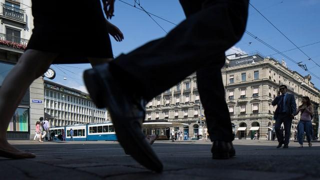 Zwei Leute gehen über den Zürcher Paradeplatz.