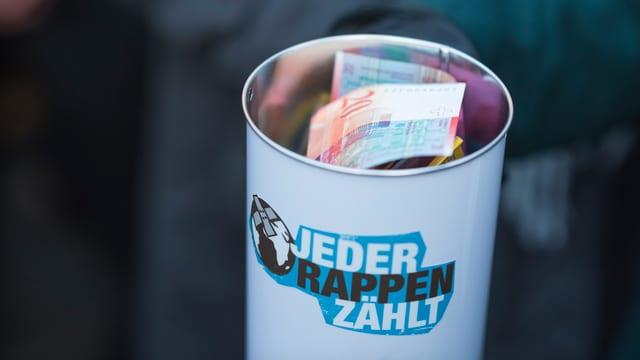 In einer Dose mit JRZ-Aufdruck liegen man mehrere Geldscheine.