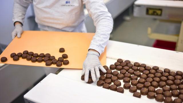 Mitarbeiterin sortiert frisch produzierte Pralinen.