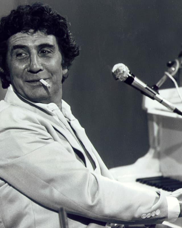 Bécaud spielt Klavier mit Zigarette im Mund.