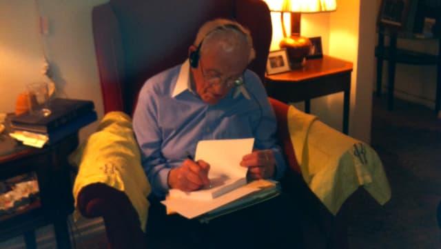 Werner Kleeman sitzt in einem Sessel und schreibt eine Widmung in ein Buch.