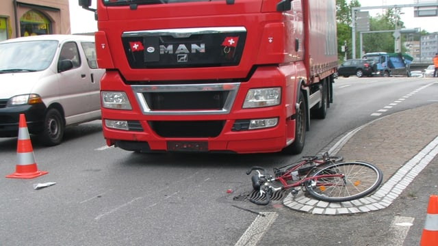 Vorne rechts liegt ein Fahrrad auf dem Boden, dahinter ein roter Lastwagen.
