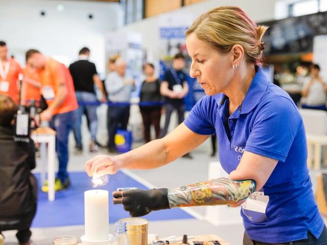 Claudia Breidbach zündet eine Kerze an. Ihr Unterarm ist mit Tattoos verziert.