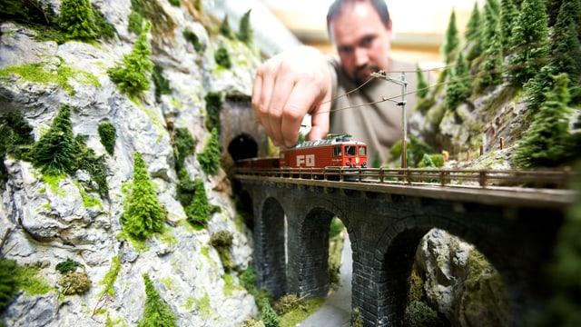 Eine Modell der Rhätischen Bahn, geführt von einer Männerhand.