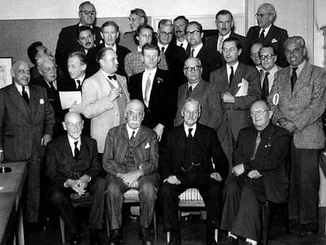Eine Gruppe von Männern versammelt sich zu einem Gruppenfoto, in ihrer Mitte ein deutlich jüngerer Mann.
