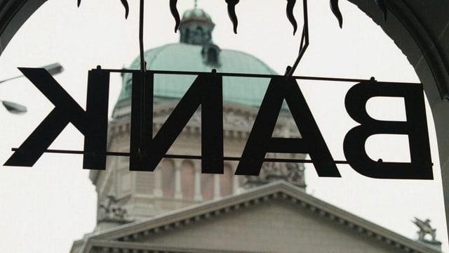 Bank-Schild spiegelverkehrt vor demr Bundeshauskuppel.