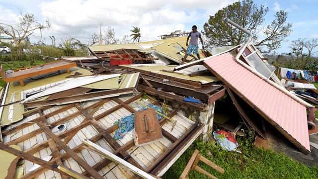 Mann steht auf Ruinen eines Hauses, Holzwände und Dach sind sichtbar.