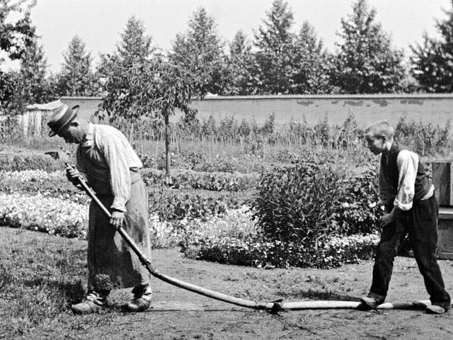 Zwei Männer im Garten, einer steht auf einem Gartenschlauch.