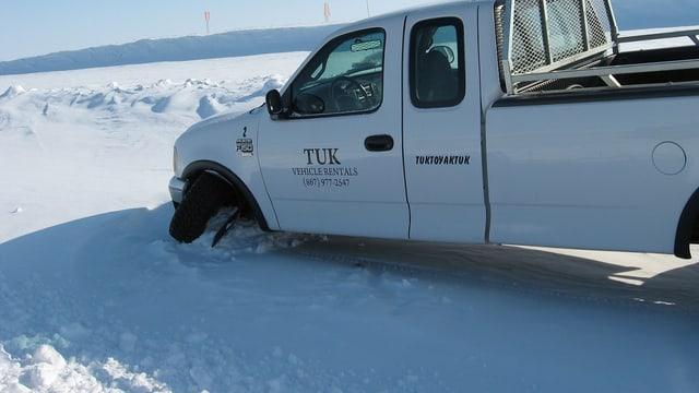 Ein weisser Truck ist im Schnee eingeklemmt.