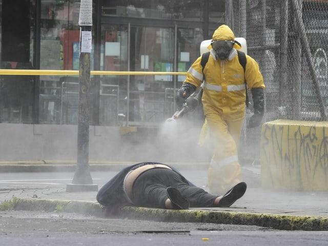 Person in Schutzanzug besprüht eine am Boden liegende Leiche mit Desinfektionsmittel.