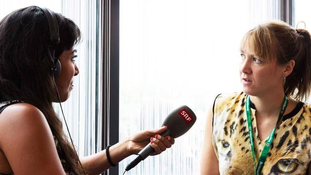 Reena Thelly hält Sophie Hunger das Mikrofon hin, die - an einer Antwort überlegend - aus dem Fenster blickt.