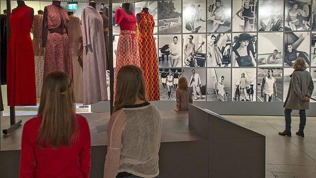 Zwei Mädchen schauen Kleider an, die an Schaufensterpuppen aufgehängt sind, im Hintergrund historische Fotografien