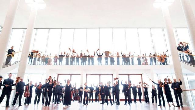 Musiker in einer grossen Halle halten ihre Instrumente in die Höhe.