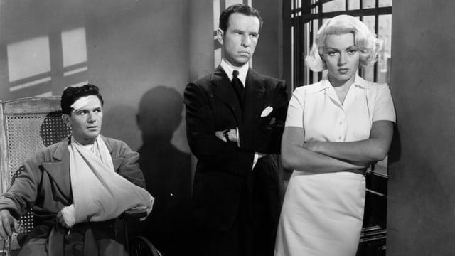 Schwarz-weiss Bild aus den 50ern mit zwei Männern und einer blonden Frau im weissen Kleid