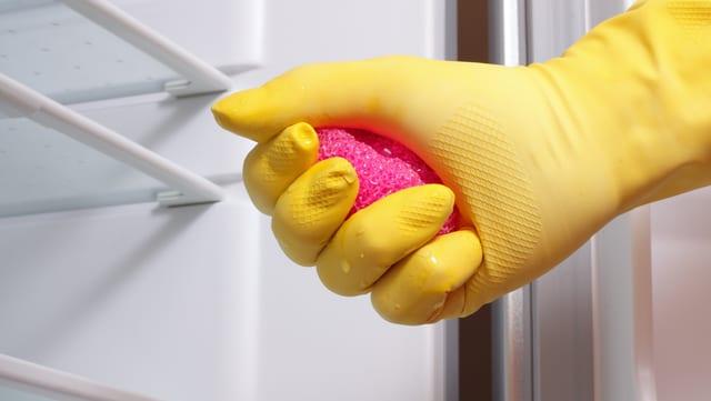 Hand mit Handschuh und Putzschwamm nähert sich einem leeren Kühlschrank