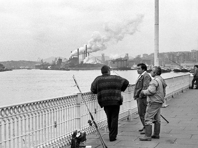 Fischer auf einer Brücke, dahinter Industriegebäude und rauchende Kamine