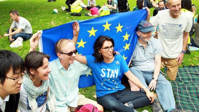 Menschen sitzen in einem Park und halten eine EU-Flagge.