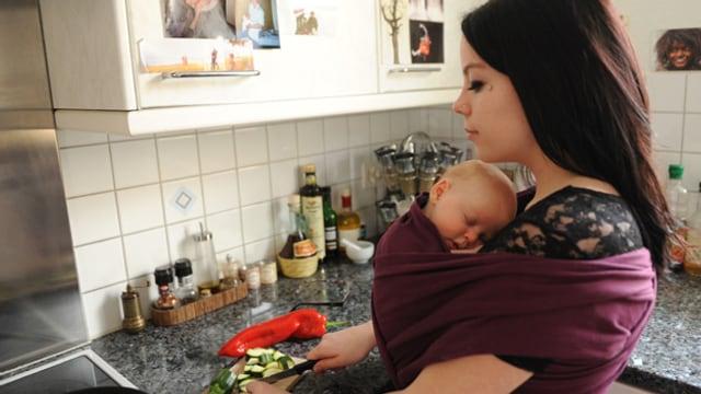 Junge Mutter beim Gemüse schneiden mit einem umgeschnallten Baby.