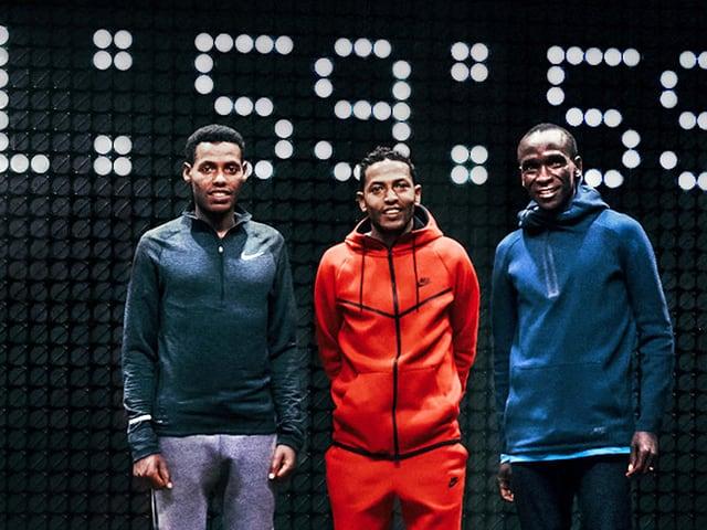 Lelisa Desisa, Zersenay Tadese und Eliud Kipchoge vor einer Anzeigetafel, die 1:59:59 anzeigt.
