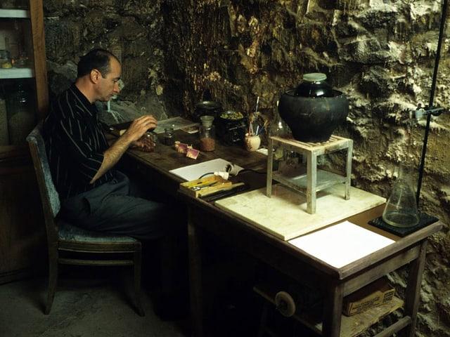 Armen Sahakijan in einem Raum mit steinigen Wänden. Er arbeitet an einem Tisch.