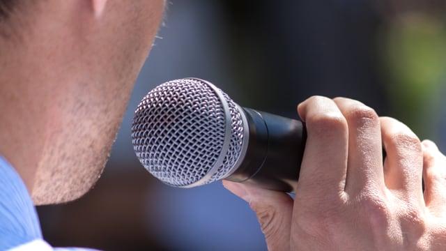 Ein Mann hält ein Mikrofon.