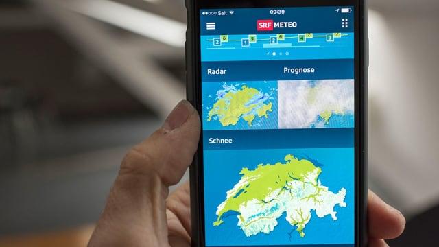 Ein Hand hält ein Handy, auf dem eine Wetter-App angezeigt wird.