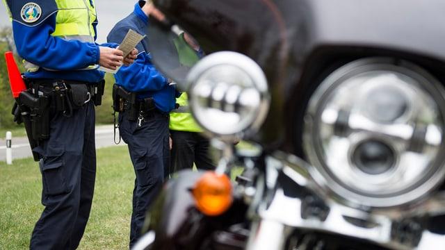 Polizisten vor einem Motorrad.