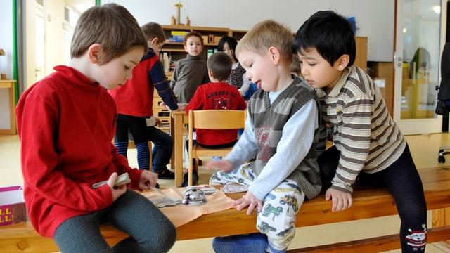 Kinder sitzen auf einem Tisch.
