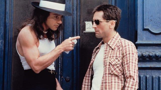 Ein Mann mit Muskelshirt und Hut redet auf einen Mann mit Sonnenbrille und Hemd ein.