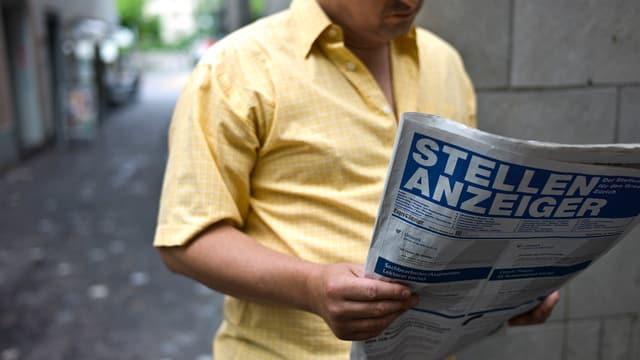 Mann in gelbem Hemd liest den Stellenanzeiger.