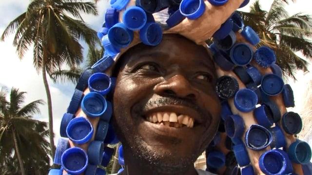 Afrikaner auf Lamu präsentiert einen aus Petflaschen-Deckeln gefertigen Hut.