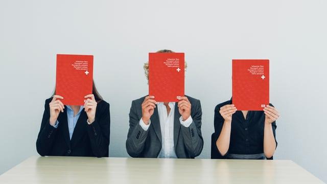 Drei Leute sitzen am Tisch und verstecken ihr Gesicht hinter drei übergrossen Schweizer Pässen.